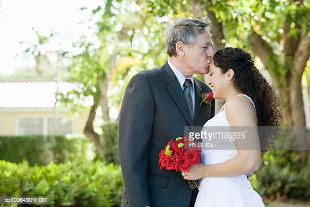 Father kissing bride on forehead outdoors, side view