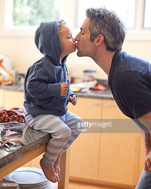 Father kissing son (1-3) on lips