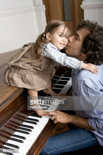 father kissing young daughter while playing piano
