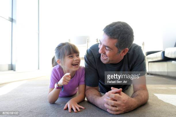 Father laughs with his daughter at home