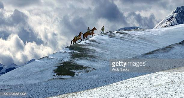Father leading horses and daughter (12-14) up snow covered mountain