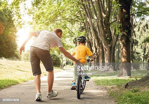 Padre Obtenga su pequeño hijo un través de una bicicleta : Foto de stock
