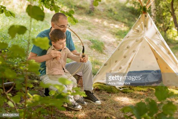 Father learning toddler boy to shoot with archery bow