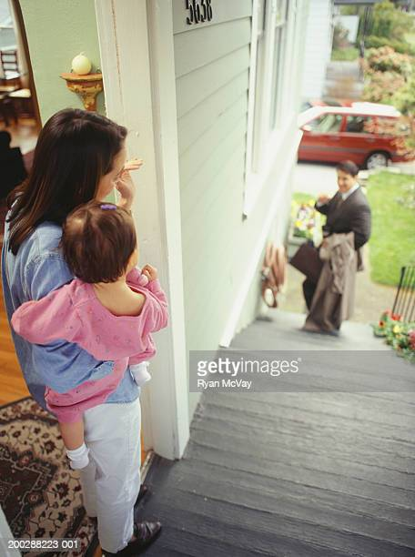 Father leaving for work, waving to wife and daughter (21-24 months), elevated view