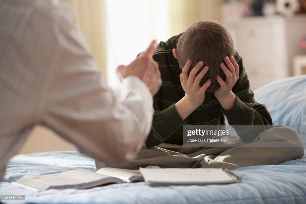 Father lecturing son in bedroom : Stock Photo