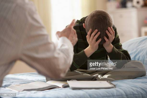 Father lecturing son in bedroom