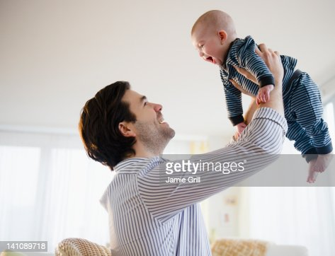 Father lifting baby boy in air : Stock Photo
