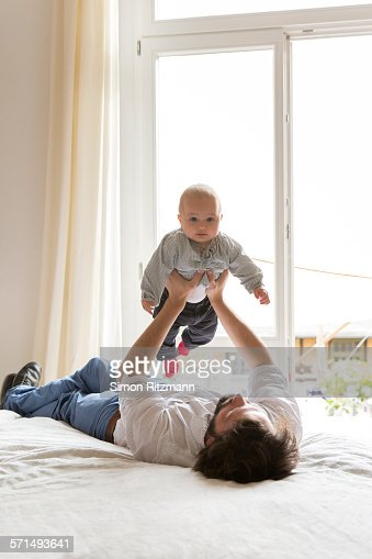 Father lifting baby boy on bed
