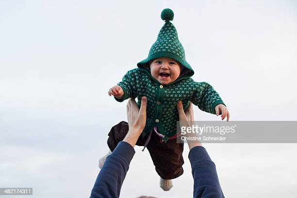 Father lifting baby daughter against sky