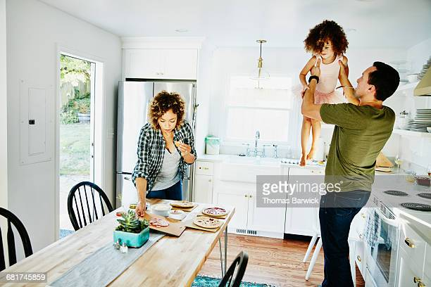 Father lifting daughter in air in kitchen