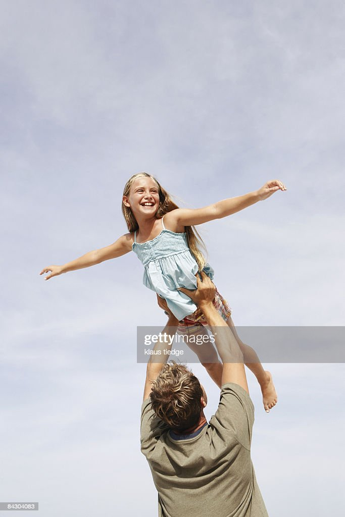 Father lifting daughter in air : Photo