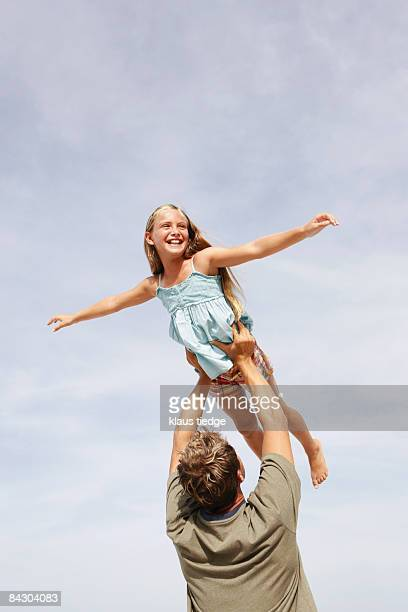 Father lifting daughter in air
