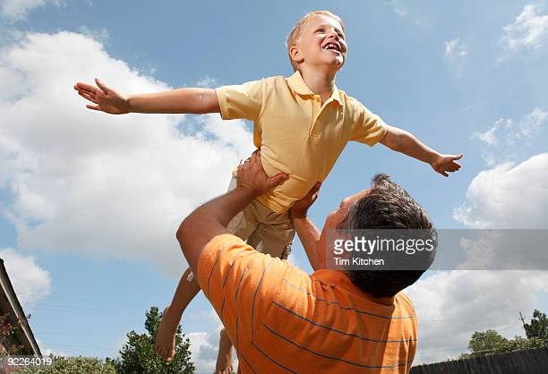 Father lifting son, boy pretending to fly
