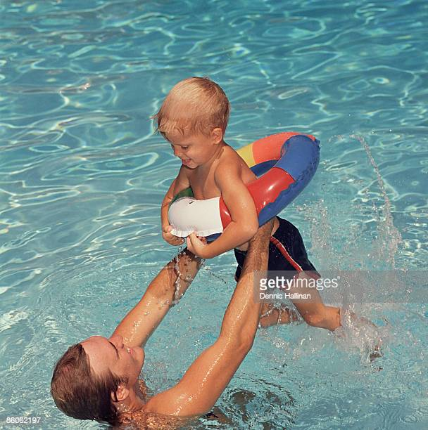 Father lifting son in swimming pool