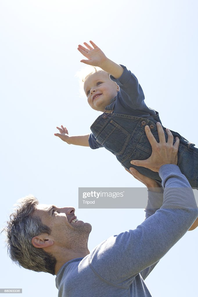 Father lifting son up in air : Stock Photo