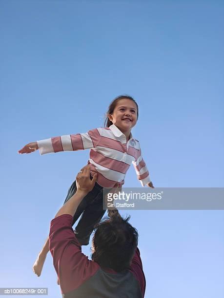 Pai levantar filha (6- 7), Vista de Ângulo Baixo contra Céu
