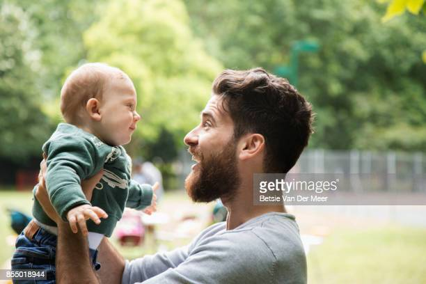 Father lifts baby up in air smiling, standing in park.