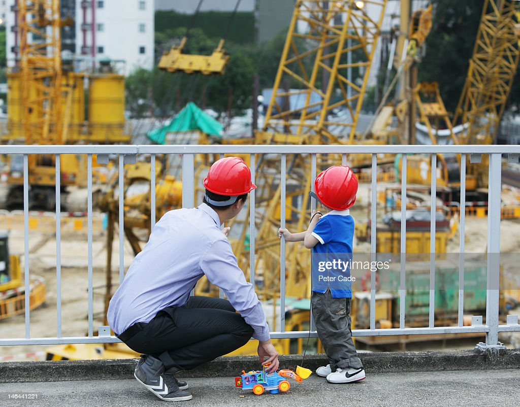 father looking at building site with young son : Stock Photo