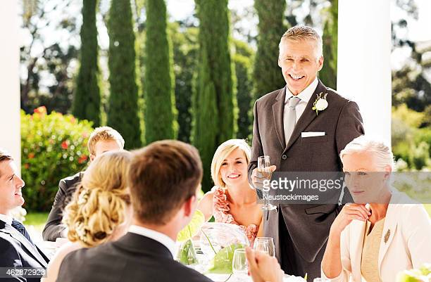 Father Looking At Couple While Giving Speech During Reception