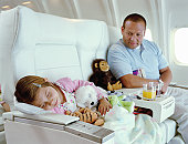 Father looking at daughter (5-7) sleeping on aeroplane