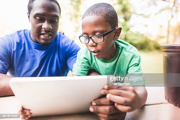 Father looking at digital tablet with son at eco camp