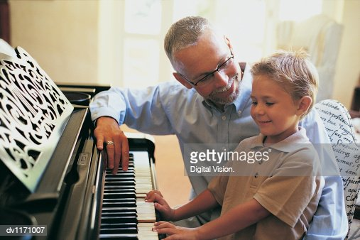 Father Looking at His Young Son Play the Piano