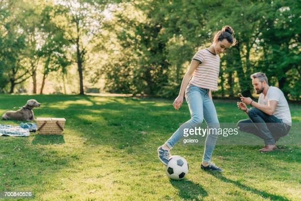 father looking at mobile while teenage daughter playing soccer on meadow