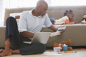 Father looking at paperwork by daughter (2-4) on sofa