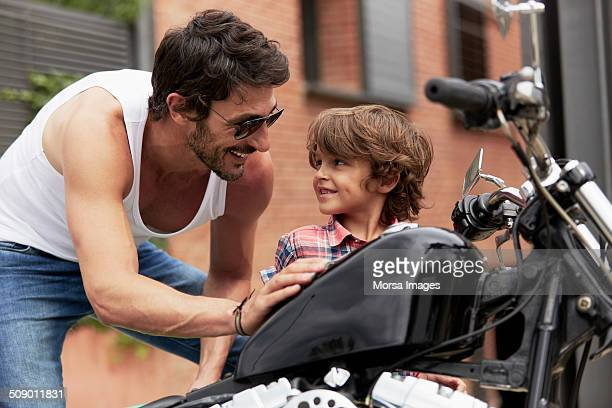 Father looking at son while touching motorbike