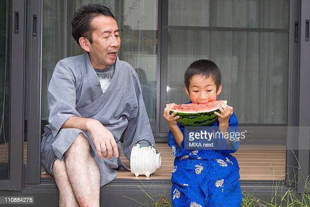 Father Looking Son Biting Watermelon