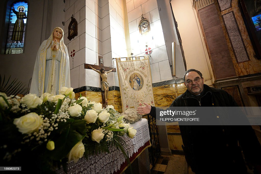 Father Lorenzo Pasquotti shows the Madonna statue found onboard the Costa Concordia cruise ship which is now on the altar of the San Lorenzo and San Massiniliano al Porto church in the Italian island of Giglio on January 11, 2013. A year on from the Costa Concordia tragedy in which 32 people lost their lives, the giant cruise ship still lies keeled over on an Italian island and its captain Francesco Schettino has become a global figure of mockery. Italy on Friday extended a series of emergency powers to deal with the removal of the Costa Concordia cruise ship wreck amid a row over delays in the salvage operation a year after the disaster. AFP PHOTO / FILIPPO MONTEFORTE