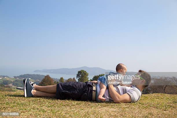 Father lying down daughter outside and smiling