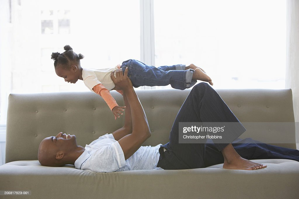 Father lying on sofa, holding daughter (2-4) up