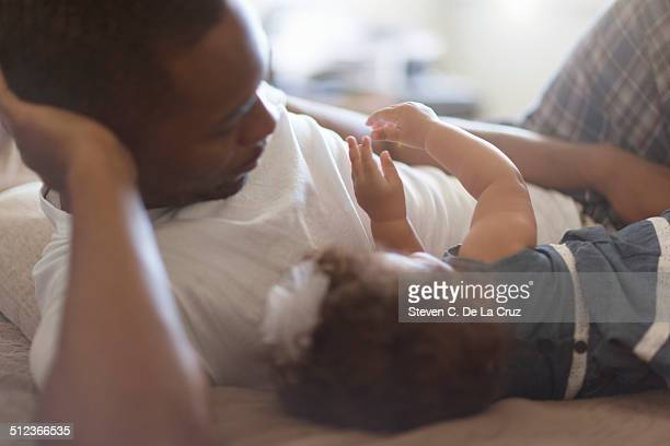 Father lying with baby daughter