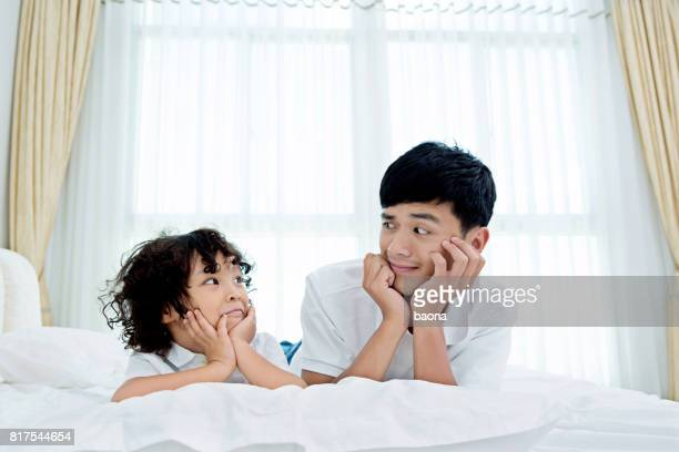 Father lying with his son in bed