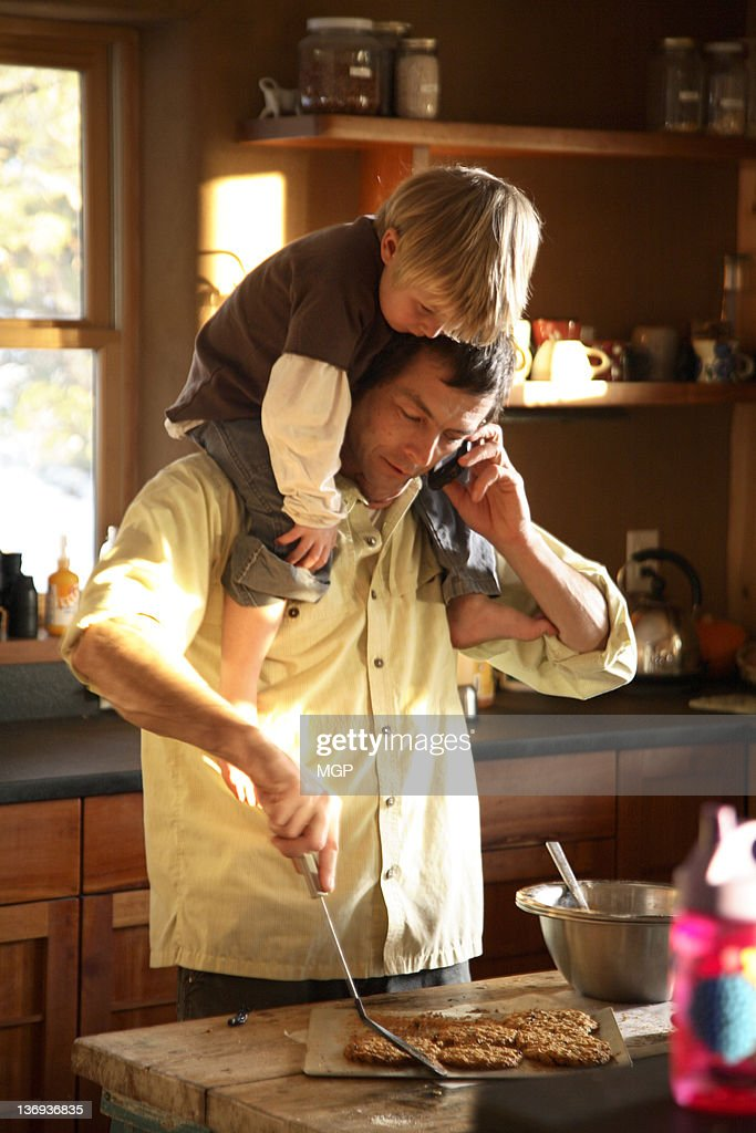 Father makes cookies and talks on cell phone with : Stock Photo