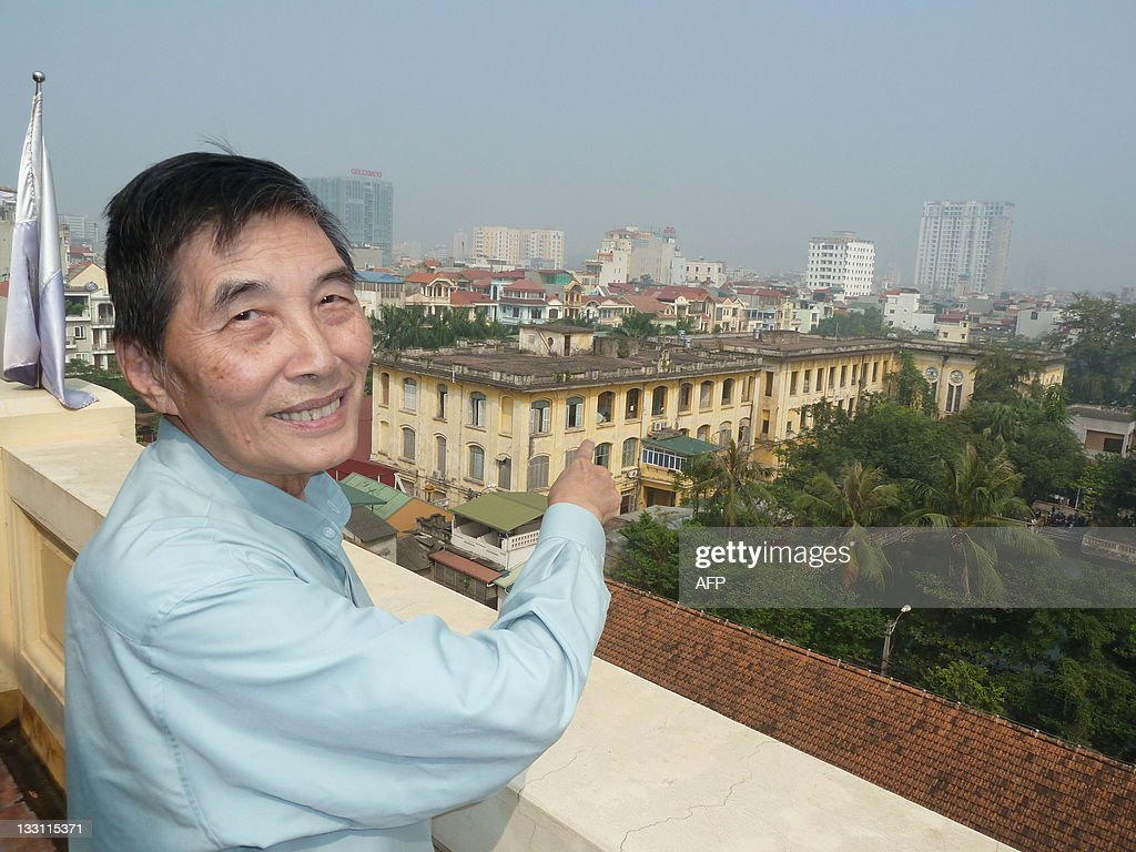 Father Matthew Phung of Thai Ha Redemptorist parish poses for a picture in Hanoi on November 17, 2011, near a hospital (yellow building to his right) which years ago was a monastery. Religious tensions have flared anew in Vietnam after communist authorities moved in November 16 to begin work on a sewage reservoir which Catholics say is on church land. The reservoir would service the hospital. AFP PHOTO / Ian Timberlake