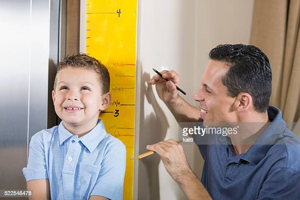 Father measuring boy's height on growth chart