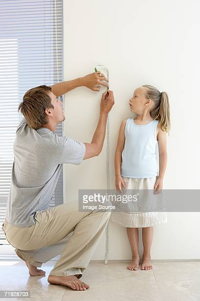 Father measuring daughters height