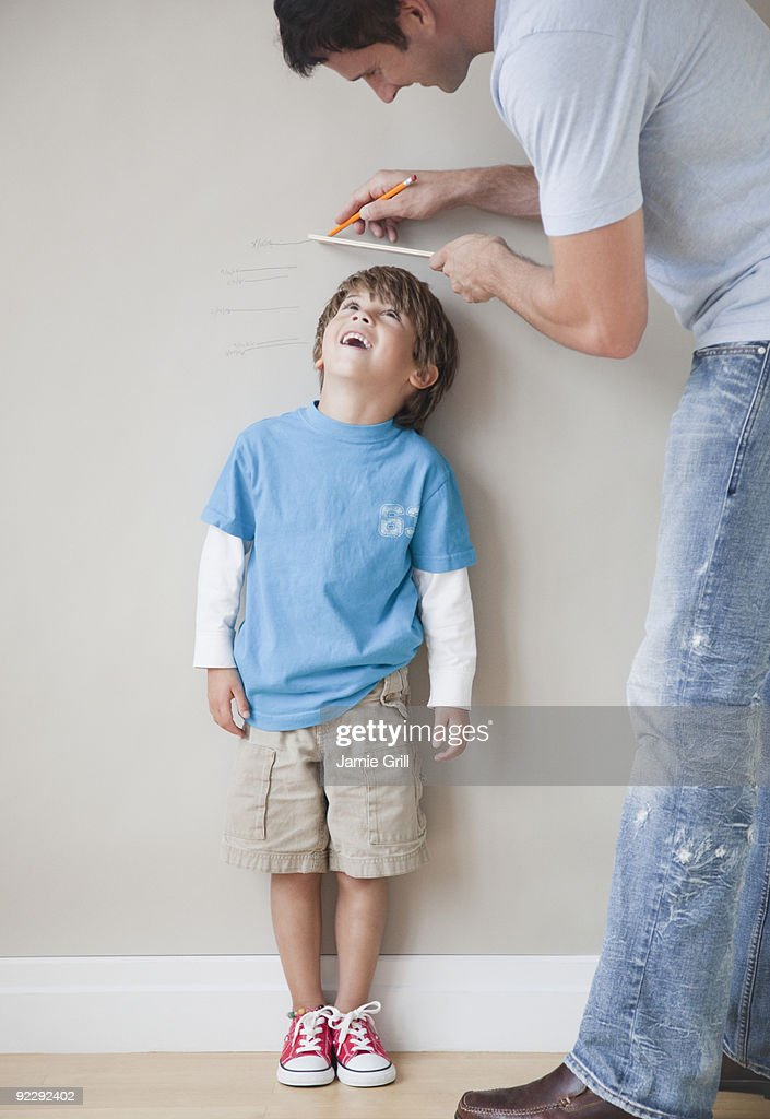 Father measuring son's height against wall : Stock Photo