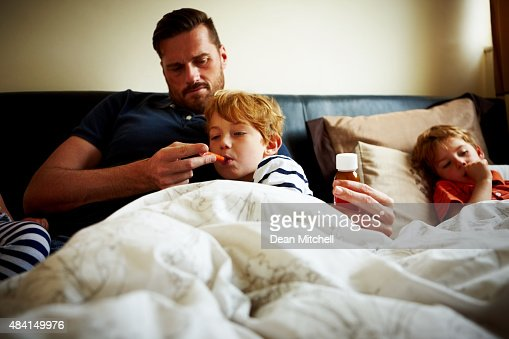 Father measuring temperature of his sick son : Stock Photo