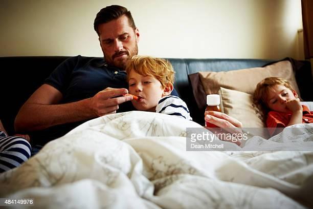 Vater messen Temperatur von seinem Kranken Sohn
