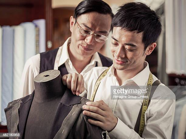 Father monitoring son in family tailoring business