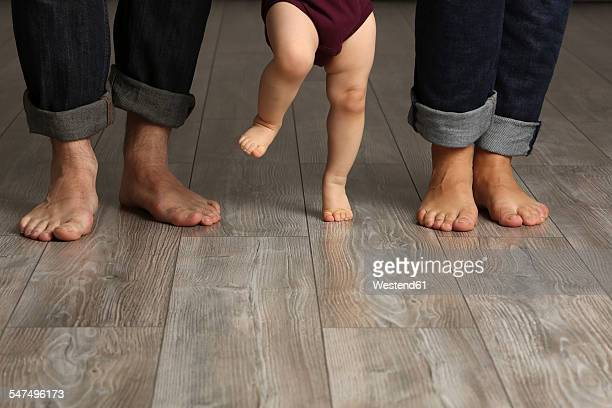 Father, mother and baby girl standing barefoot on floor