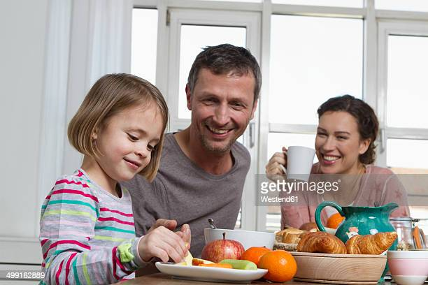 Father, mother and daughter having healthy breakfast