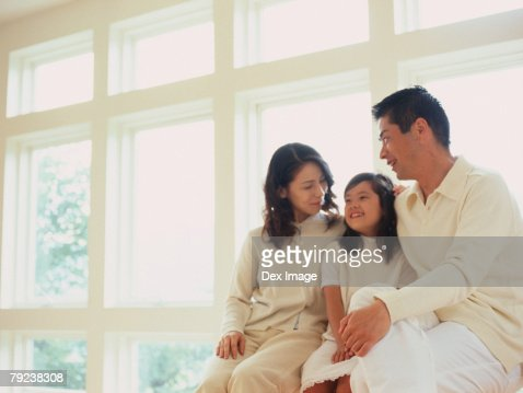 Father, mother and daughter sitting by window sill : Stock Photo