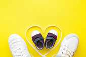 Father, mother and little kid shoes. Heart created from white shoelaces. Yellow background. Love sport together concept. Empty place for lovely, motivational, inspirational text, quote or sayings.