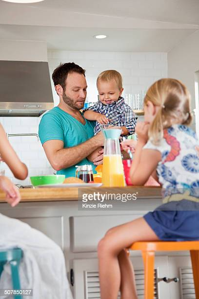 Father multi tasking breakfast with son and daughters