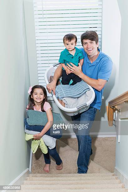 Father multitasking, doing laundry and caring for kids