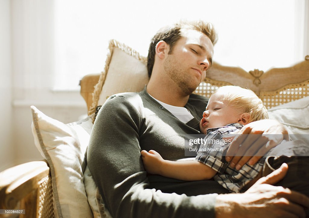 Father napping with son on sofa : Stock Photo